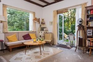Eenvoudige maar knusse woonkamer met openslaande deuren naar terras