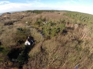 Luchtfoto in de winter: de Duindoorn linksonder met bos en strand op achtergrond